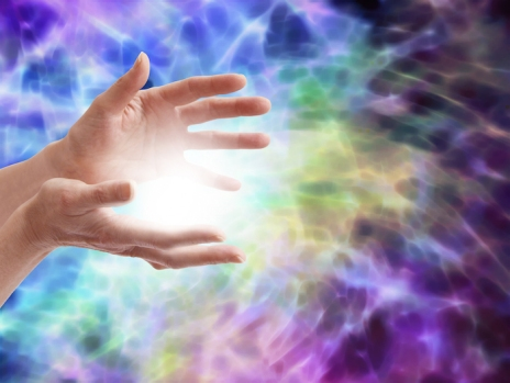 Female healer's open hands with ball of white light on a watery effect electrifying purple and blue background